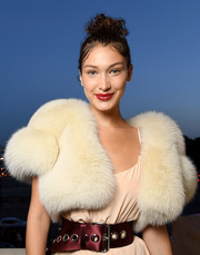 Bella Hadid highlighted her tiny waist with an oversized burgundy satin belt at the Miu Miu Cruise show.