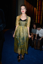 Ulyana Sergeenko looked head-to-toe sweet at the Miu Miu fashion show in a sheer yellow dress and black evening sandals with bowed ankle straps.