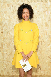 Gugu Mbatha-Raw paired a white leather clutch with a cute yellow mini dress for the Miu Miu Spring 2020 show.