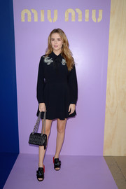 Zoey Deutch completed her look with a quilted shoulder bag, also by Miu Miu.