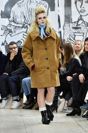Elle Fanning bundled up in a bulky camel coat for her turn on the Miu Miu catwalk.