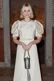 Lucy Boynton paired a tasseled silver purse with an ivory dress for the Miu Miu Women's Tales dinner.