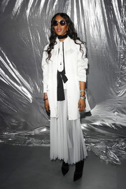 Naomi Campbell covered up with a white satin coat for the Moncler Genius show.