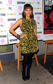 Rashida Jones paired her flirty yellow floral print dress with black satin lace up boots.