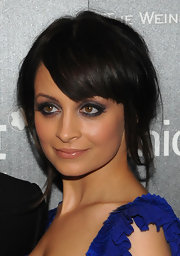 Nicole Richie draws focus to her eyes with a pewter toned smoky eye. The shadow lines her lower lids for extra drama.