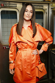 Kacey Musgraves styled her trench coat with a pair of cuff bracelets for the Moschino Pre-Fall 2020 show.