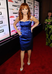 Reba McEntire paired her sultry blue satin corset dress with white peep toe pumps.
