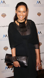 Tia Carrere paired her sheer black dress with a metallic silver clutch and matching statement necklace.