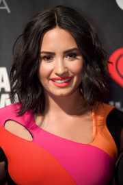 Demi Lovato embraced color, pairing bright orange lipstick with her multi-hued outfit.
