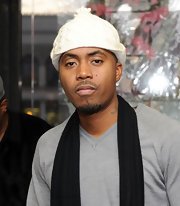 Nas opts for a white pom pom beanie for this winter look.