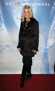 Monica Potter bundled up in a ruffled trench and black leather knee high boots.