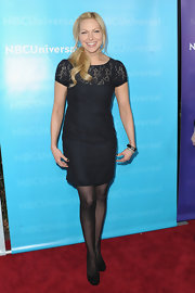 Laura topped off her look with sheer black tights and classic black pumps.