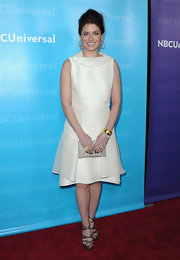 Debra Messing accessorized her white dress with metallic strappy sandals.