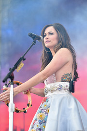 Kacey Musgraves revealed her colorful tattoo, which features a blue anchor between a pair of yellow roses and the word 'Older' below them, when she wore this backless dress at the NCAA March Madness Music Festival.