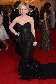 Amy Poehler's corset gown at the Met Gala had an extravagant feather train and was made from perforated leather.