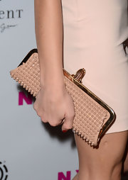 Ashley Carried this spiked nude clutch with a gold frame to match her cream dress.
