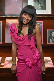 Naomi Campbell attended the launch of her book wearing a gold bracelet and a frilly fuchsia gown.