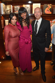 Naomi Campbell went ultra frilly in an asymmetrical, bow-adorned fuchsia gown for her book launch.