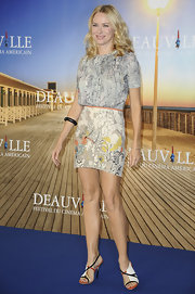 Naomi Watts accessorized her floral frock with strappy sandals with yellow and orange accents.