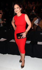 Gloria accessorized her fitted red dress with metallic cap-toe platform pumps.