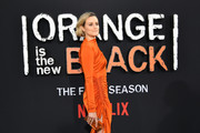 Taylor Schilling accessorized with an orange box clutch to match her dress at the premiere of 'Orange is the New Black' season 7.