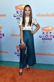 For a bit of shimmer, Maddie Ziegler accessorized with a tasseled silver clutch by Kate Spade.