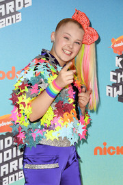 JoJo Siwa accessorized with a rainbow wristband to match her colorful outfit at the 2019 Kids' Choice Awards.