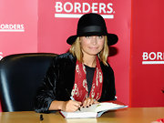 "Nicole Richie signs a copy of her book ""Priceless"" with short square nails painted dark purple."