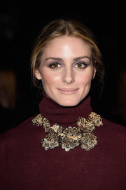 Olivia Palermo's gold flower statement necklace at the Nina Ricci show put a striking finish to her burgundy turtleneck.