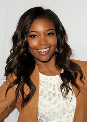Gabrielle Union always glows. Here she rocks her long loose waves with a sleek side part at the launch of Nintendo 3DS. Honey blond highlights lighten up the look.