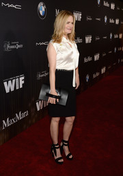 Jennifer Jason Leigh accessorized her look with a black leather hand-strap clutch.