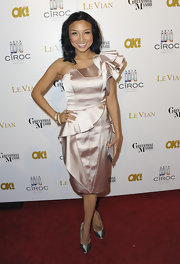 Jeannie Mai was all about femininity at the OK! Magazine pre-Oscar party in a frilly gold one-shoulder dress with a ruffle sleeve and a peplum waist.
