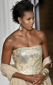 It was hard to decide which one was more stunning--Michelle Obama's fleur de lys gemstone drop earrings, her glam updo, or her sequined evening dress.