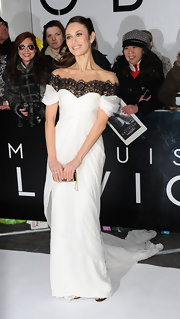 Olga Kurylenko is simply radiant in this floor-length gown featuring a gathered sweetheart bodice, black lace neckline, and a draped full-length skirt.