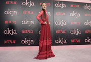 Lily Collins went for bohemian glamour in a long-sleeve red Valentino gown at the New York premiere of 'Okja.'
