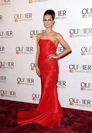 Kara wears a strapless red organza gown with a dramatic layered train at the Olivier Awards.