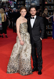 Rose Leslie was a classic beauty in a strapless gold gown by Malene Oddershede Bach at the Olivier Awards.