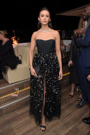Nina Dobrev finished off her look with a black satin clutch.