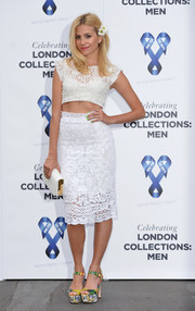 Pixie Lott styled her outfit with an elegant white leather clutch.