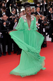 Lupita Nyong'o made a triumphant return to the red carpet in a breathtaking jade-green Gucci gown with a plunging neckline and flower-embellished shoulders.