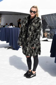 Ashlee Simpson teamed a monochrome fur coat with ripped jeans for her Celebrity Ski & Smile Challenge look.