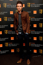 Eddie Redmayne looked casual and hip in a dark brown blazer paired with classic fit jeans.