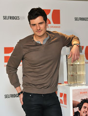Orlando Bloom launched the new Boss Orange fragrance in a taupe brown v-neck sweater.