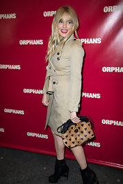 Sienna Miller styled her outfit with an adorably chic heart-print clutch by Burberry.
