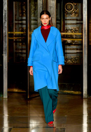 Bella Hadid cut a colorful figure in a bright blue coat and teal pants combo while walking the Oscar de la Renta show.