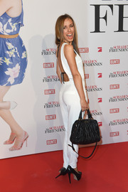 Annemarie Carpendale styled her jumpsuit with a chic ruched leather cross-body tote by Miu Miu.
