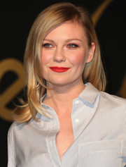 Kirsten Dunst finished off her look with a vibrant red lip.