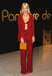 Poppy Delevinge's ochre M2Malletier velvet bag made a striking contrast to her red suit.