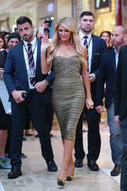 Paris Hilton complemented her chic dress with gold and black cap-toe platform pumps by Gina.