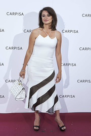 Penelope Cruz attended the Carpisa photocall wearing a white David Koma midi dress with a strappy neckline and black mesh panels on the skirt.